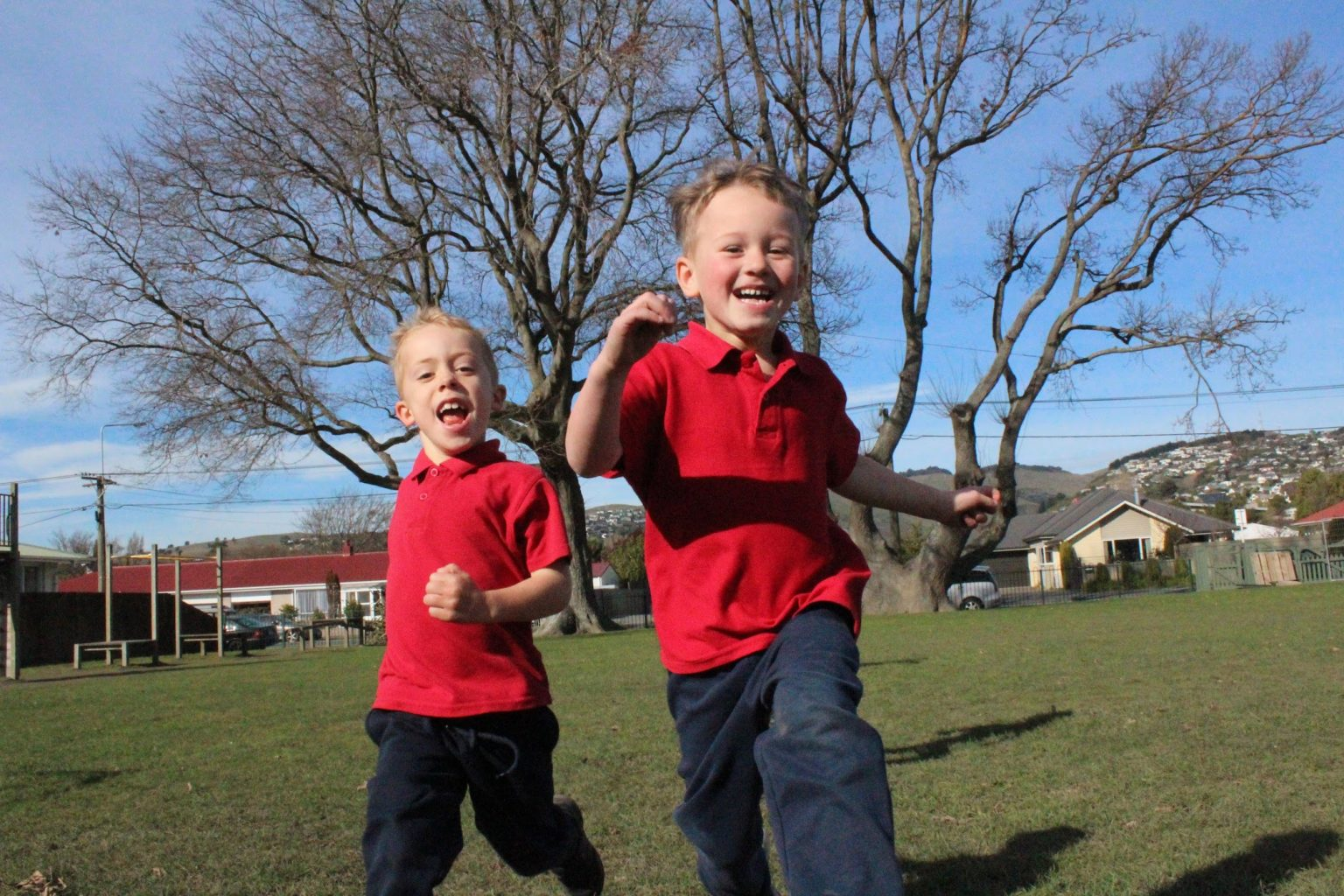 Two Somerfield Te Kura Wairepo male students running on school field
